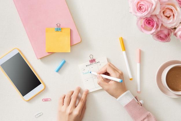 白いオフィスのデスクトップに配置された空白のスパイラルメモ帳で書く実業家の手の上面図