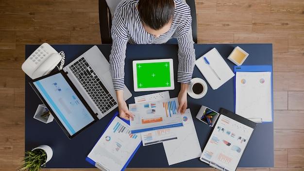 Вид сверху на бизнесвумен, сидящую за столом, работающую в управленческом партнерстве, анализирующую статистику компании ...