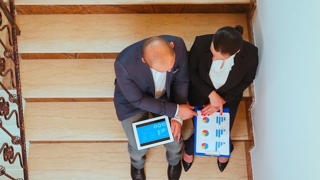 タブレットを探しているビジネスビルの階段で企業のエグゼクティブマネージャーと話している実業家の上面図。現代のオフィスで残業しているチームのプロの成功した起業家