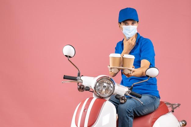 パステル調の桃の背景に注文を示すスクーターに座っている帽子をかぶったマスクを着た忙しい宅配便のトップビュー