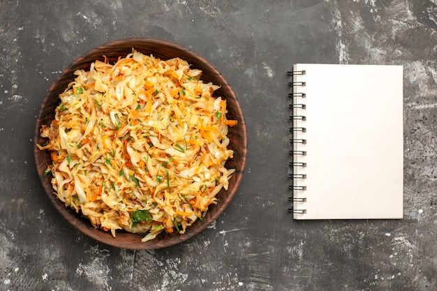 Вид сверху капусты с морковью миска капусты с морковью рядом с ноутбуком