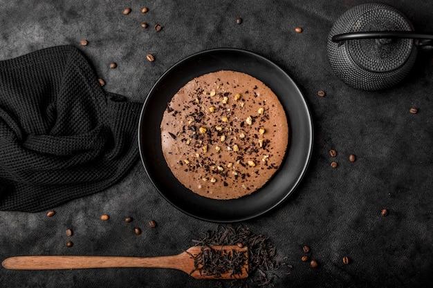 ヘラとコーヒー豆の皿の上のケーキのトップビュー