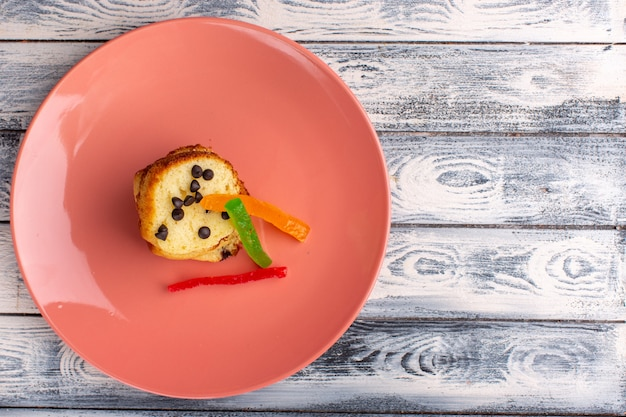 光の表面にチョコチップとマーマレードが付いている茶色のプレート内のケーキスライスの上面図