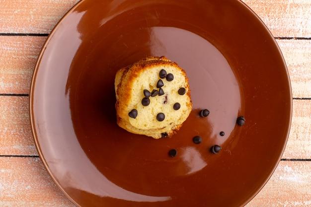 Вид сверху на кусок торта внутри коричневой тарелки с шоколадными чипсами на светлой поверхности
