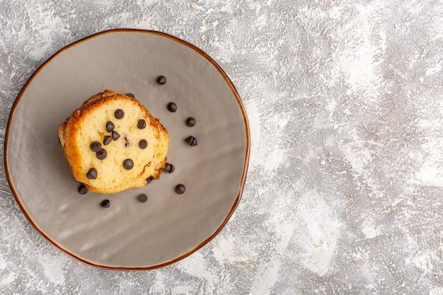 Вид сверху на кусок торта внутри тарелки с шоколадной стружкой на светлой поверхности
