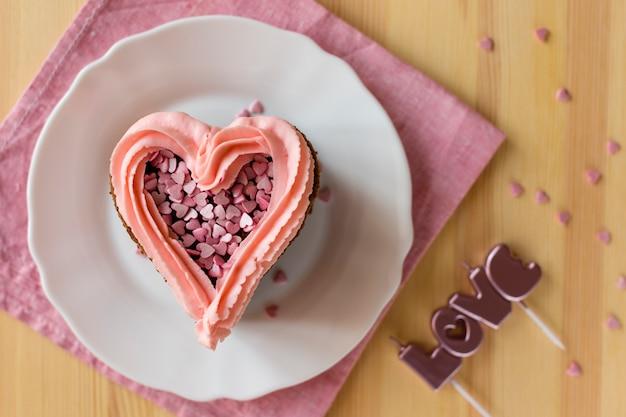 Вид сверху кусочек торта с глазурью и свечами