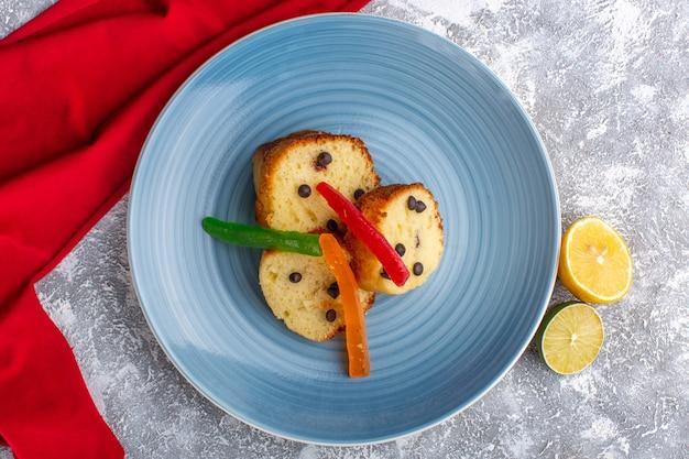 Вид сверху на кусочки торта внутри синей тарелки с шоколадной стружкой и мармеладом на деревенской серой поверхности