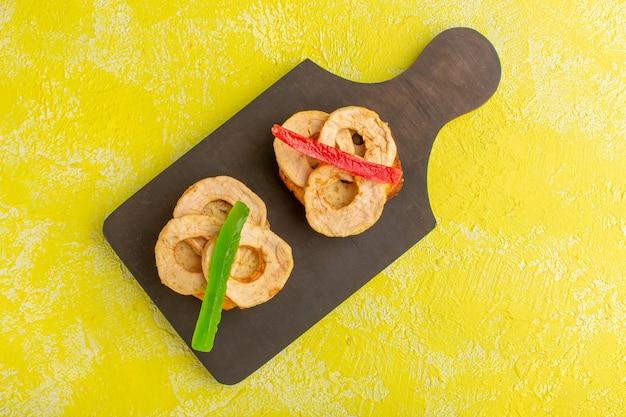 黄色の表面に乾燥パイナップルリングとマーマレードのケーキスライスの上面図