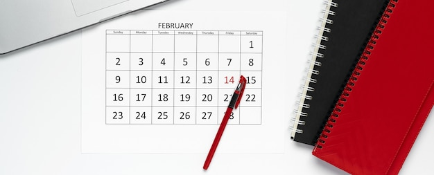 ペン、メモ帳、ノートパソコンを載せた2月のカレンダーの上面図。テンプレート、オフィスコンセプト