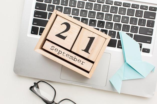 Вид сверху календаря с ноутбуком и бумажным голубем