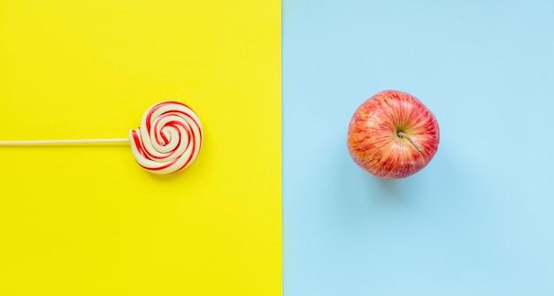 Вид сверху конфеты на палочке против свежего красного яблока на ярком двухцветном ярком желто-синем фоне. плоская диета и концепция здорового образа жизни