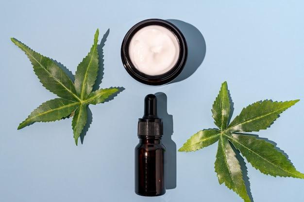 대마초 얼굴 혈청 및 크림 또는 오일 스포이드 개념의 상위 뷰. 천연 화장품. 이중 대리석과 검정색 배경에 cbd 오일, thc 팅크 및 대마 잎