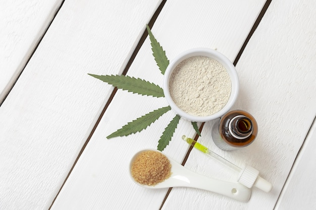 大麻注入製品の上面図マリファナ小麦粉砂糖油om白い木製の背景