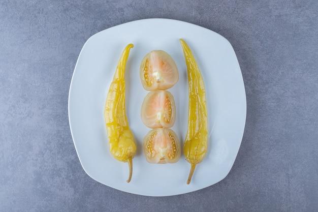 Вид сверху консервированного зеленого перца и ломтиков помидора на белой тарелке.