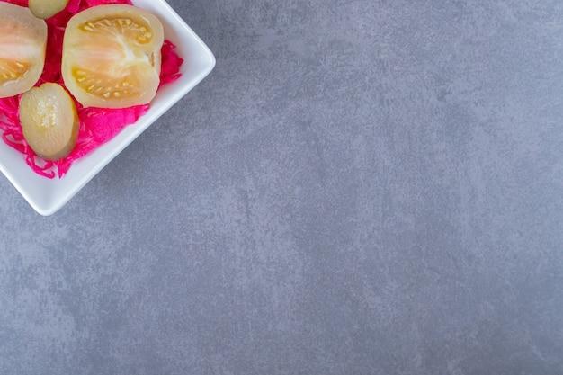 하얀 접시에 통조림된 녹색 토마토 조각의 상위 뷰.