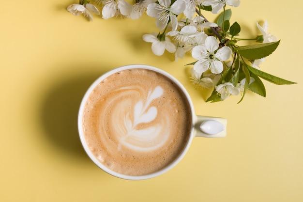 Вид сверху капучино в красивой чашке с веткой цветущей вишни
