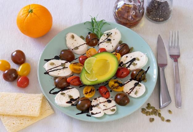 カプレーゼサラダの上面図。チーズモッツァレラチーズと小さなトマト、コショウ、バルサミコ酢のプレート。健康的な食事を補完するハーフアボカドとオレンジ