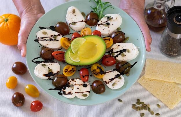 カプレーゼサラダの上面図。女性の手は、チーズモッツァレラチーズと小さなトマト、コショウ、バルサミコ酢のプレートを持っています。健康的な食事を完成させるための半分のアボカド