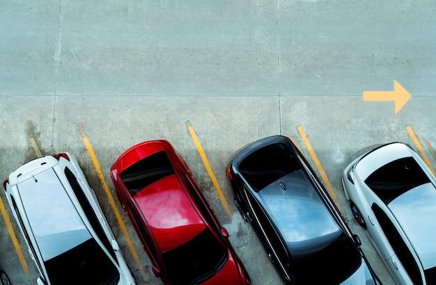 거리의 교통 표지의 노란 선으로 콘크리트 자동차 주차장에 주차 된 자동차의 상위 뷰. 주차 공간에서 행에 자동차의보기 위의. 사용 가능한 주차 슬롯이 없습니다.