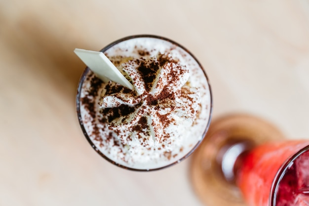 Вид сверху карамельного молочного коктейля, наполненного взбитыми сливками и шоколадным порошком.