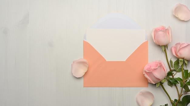 カード、パステル封筒、コピースペース、大理石の机に飾られたピンクのバラの花の上面図