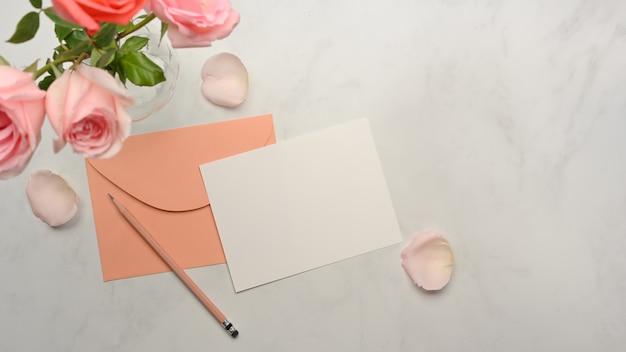 カード、パステル封筒、鉛筆、大理石の机に飾られたピンクのバラの花の上面図