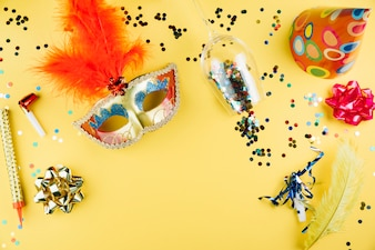 Top view of carnival mask with decoration material and over yellow background