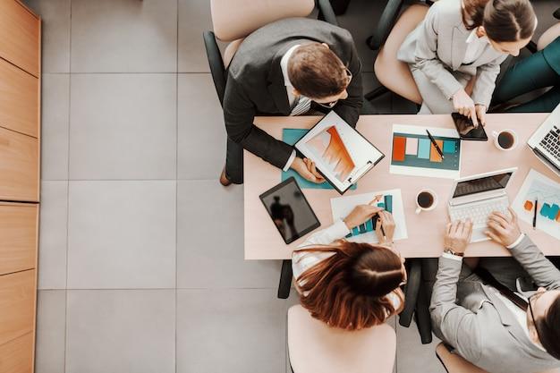Вид сверху кавказских деловых людей в формальной одежде, сидящих в зале заседаний за столом и анализирующих данные. на столе ноутбуки, графики, планшеты и документы.