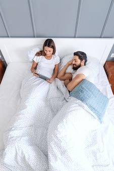 Вид сверху кавказской пары в постели, смотреть видео на планшете. интерьер спальни.