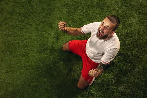 草の緑の背景に白人サッカー選手またはサッカー選手の上面図。若い男性のスポーツモデルのトレーニング、練習。ボールを蹴る、攻撃する、捕まえる。スポーツ、競争、勝利の概念。