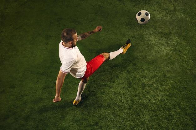 草の緑の背景に白人のフットボールまたはサッカー選手の平面図です。若い男性のスポーツ モデルのトレーニング、練習。ボールを蹴る、攻撃する、キャッチする。スポーツ、競争、勝利のコンセプト。