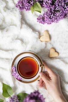 ベッドの上のハート型のクッキーとお茶のカップを持っている白人の手の平面図です。