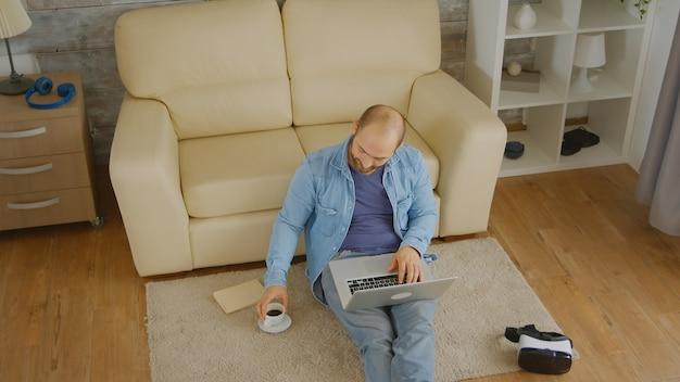 노트북 작업과 커피 한 잔을 즐기는 백인 남자의 상위 뷰