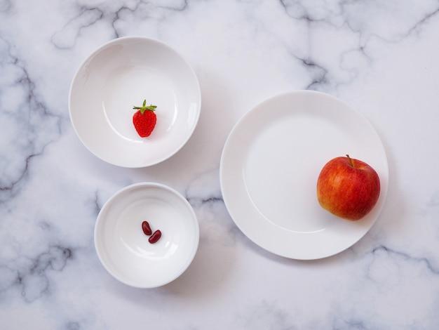 대리석 테이블에 고립 된 붉은 과일 다이어트 건강 식품 세라믹 플레이트와 흰색 그릇의 상위 뷰