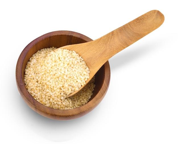 Вид сверху цельного зерна сушеных пищевых продуктов с белыми семенами кунжута в деревянной ложке на миске, изолированной на белом.