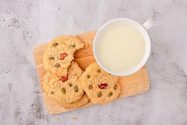 シリアルクッキーの上面図はまな板の上に積み重ねられ、アーモンド、レーズン、ヒマワリの種、カボチャの種、全粒穀物をトッピングしたクッキーです。