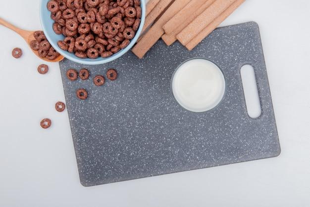 Вид сверху зерновых в миске и в деревянной ложке с печеньем на разделочной доске на белом фоне