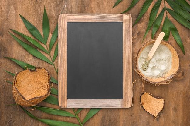 Вид сверху на доске с порошком в скорлупе кокосового ореха и листьями