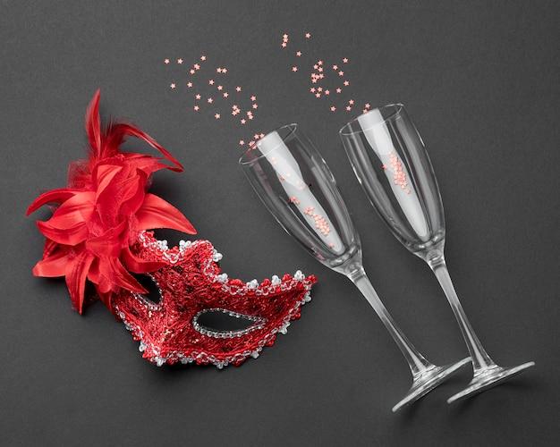 Вид сверху бокалов для шампанского и карнавальной маски с перьями