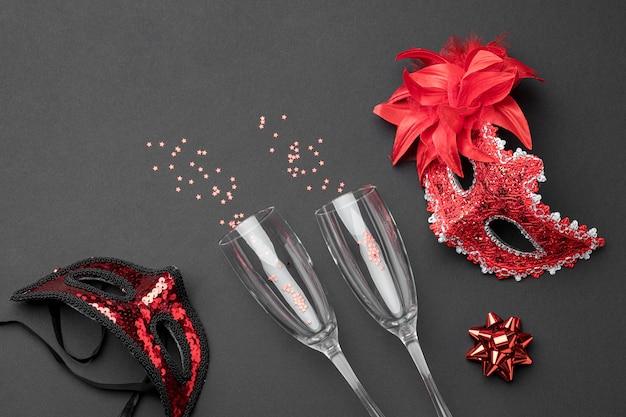 Вид сверху бокалов для шампанского и карнавальных масок с перьями