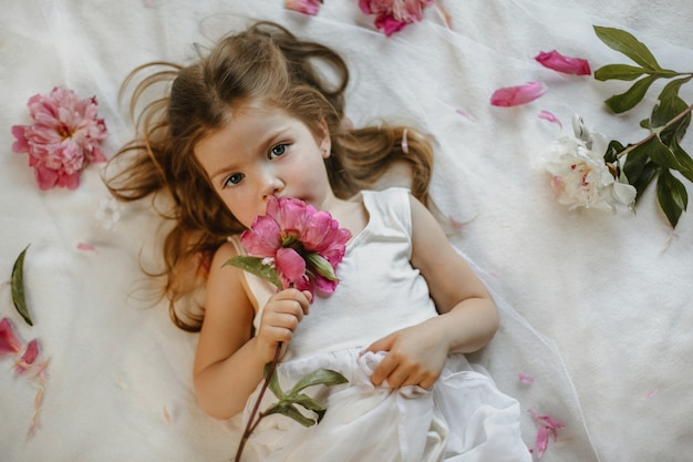 Вид сверху очаровательной растущей крошечной девочки, держащей тусклый розовый пион, лежащей на белой простыне, в окружении свежих цветов, серьезно выглядящей прямо