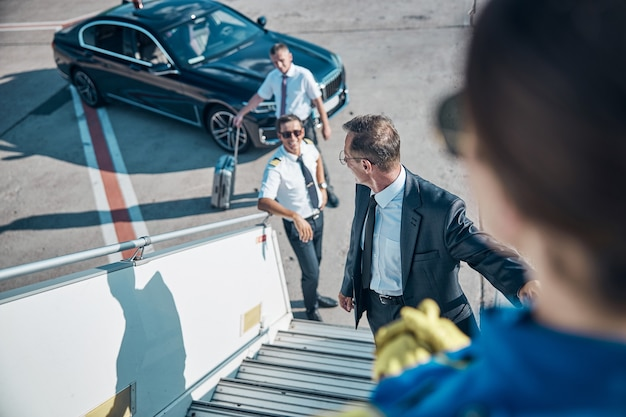 旅行で飛ぶために階段を上るビジネスマンに会う陽気な飛行機のスタッフの上面図