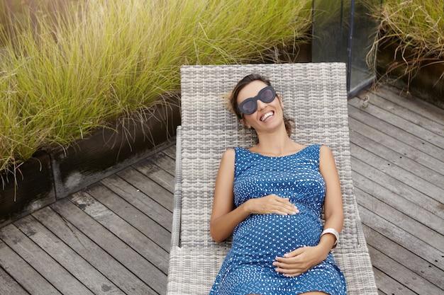 Вид сверху веселой беременной женщины в стильных оттенках, лежащей на шезлонге и держащейся за руки на животе. улыбающаяся красивая женщина ожидает ребенка, отдыхающего во время каникул на курорте