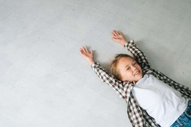 カメラを見て手を上げて白い床に横たわっている陽気なかわいい子の女の子の上面図