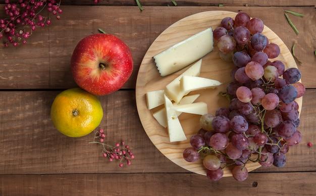 Вид сверху сырной тарелки с виноградом, мандарином и красным яблоком, на деревянном столе