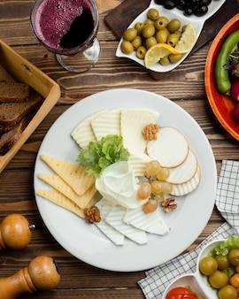 Вид сверху на сырную тарелку с красным вином