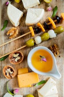 Взгляд сверху сыра установленного как пармезан бри и чеддер с грецким орехом масла оливки на разделочной доске на деревянной предпосылке