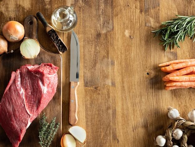 Вид сверху нож шеф-повара рядом с куском красного мяса на деревянном столе. скопируйте доступное пространство.