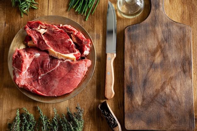 木製のテーブルの上の赤身の肉と緑の野菜の大きな塊の横にあるシェフナイフの上面図。新鮮な肉。