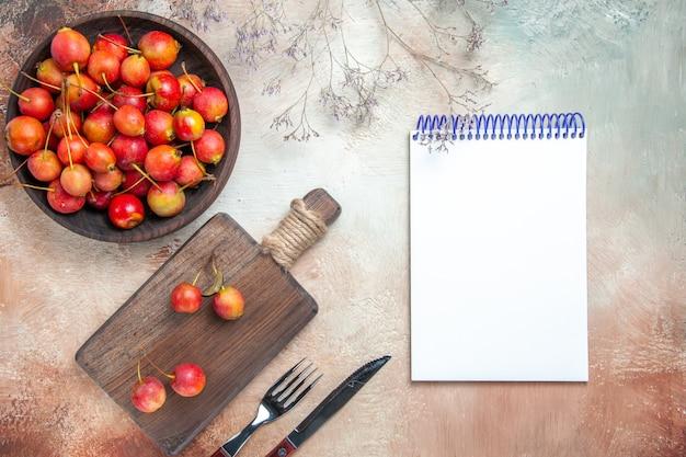 Вид сверху ягод вишни на доске, миска с вишней, вилка, нож, белый блокнот